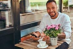 En trendig afrikansk amerikan uppsökte manligt sammanträde nära en coffee shop med en kopp kaffe, genom att använda en smartphone arkivfoto