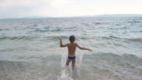 En trevlig liten grabbspring från stranden till Adriatiskt havet och dykning in i vattnet dalmatia croatia lager videofilmer