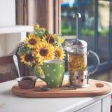 En trevlig sommarstilleben Örtteavkok med cookires i ett kafé framme av blommabuketten royaltyfria foton