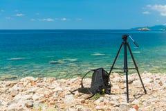 En tripod och en ryggsäck på bakgrunden av havet arkivbild