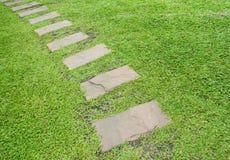 En trottoar och ett grönt gräs. Arkivfoton
