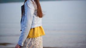 En tunn tonåring i modern kläder strosar längs en öde shoreline med sand arkivfilmer