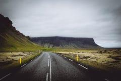 En tunn väg i ett grönt fält med kullar och grå molnig himmel arkivbilder