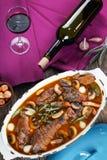 En tupp som låtas småkoka i rött vin Arkivfoto