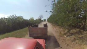 En tur med bilen på en grusväg, ett hivamoln av damm från hjulen stock video