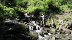 En turist dricker vatten från en bergström lager videofilmer