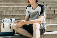 En turist eller en student sitter på trappan, vilar och använder en mobiltelefon arkivbilder