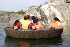 En turist- familj på en coracleritt på Hogenakkal faller, Tamil Nadu Royaltyfri Foto
