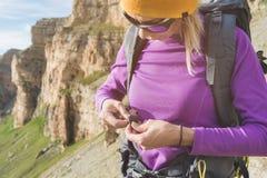 En turist i solglasögon sätter en ryggsäck i naturen på bakgrunden av epos vaggar att förbereda sig för trekking med fotografering för bildbyråer