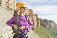 En turist i solglasögon sätter en ryggsäck i naturen på bakgrunden av epos vaggar att förbereda sig för trekking med arkivfoto