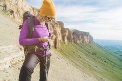 En turist i solglasögon sätter en ryggsäck i naturen på bakgrunden av epos vaggar att förbereda sig för trekking med royaltyfria bilder