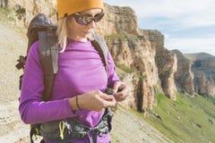 En turist i solglasögon sätter en ryggsäck i naturen på bakgrunden av epos vaggar att förbereda sig för trekking med royaltyfria foton