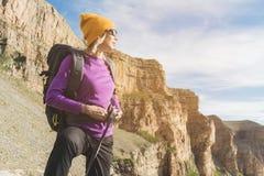 En turist i solglasögon sätter en ryggsäck i naturen på bakgrunden av epos vaggar att förbereda sig för trekking med royaltyfri foto