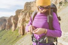 En turist i solglasögon sätter en ryggsäck i naturen på bakgrunden av epos vaggar att förbereda sig för trekking med royaltyfri bild