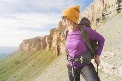 En turist i solglasögon sätter en ryggsäck i naturen på bakgrunden av epos vaggar att förbereda sig för trekking med arkivbild