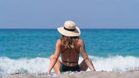 En turist i en svart baddräkt ser ut till havet i Turkiet Royaltyfri Bild