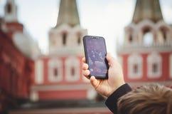 En turist- man tar bilder på telefonen i röd fyrkant i Moskva fotografering för bildbyråer