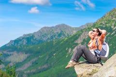 En turist med en ryggsäck på bakgrunden av den härliga mountaien Royaltyfri Foto