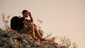 En turist med en stor ryggsäck sitter på vaggar och vilar på solnedgång lager videofilmer