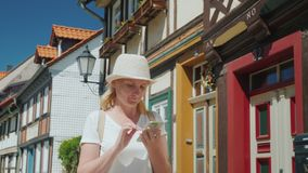 En turist med en telefon i hennes händer promenerar den härliga gatan av en europeisk stad stock video