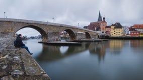 En turist sitter vid floden och blickarna på staden arkivfoton