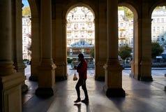 En turist som går till och med det populärt, maler kolonnaden i den gamla staden av Karlovy varierar arkivbild