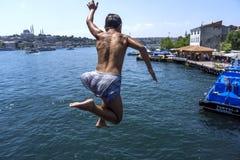 En turkisk pojke hoppar från den Galata bron in i det guld- hornet i Istanbul i Turkiet Royaltyfria Bilder