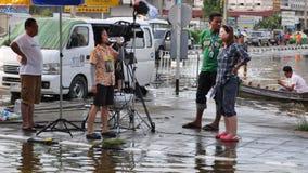 En TVbesättning är i en översvämmad gata av Pathum Thani, Thailand, i Oktober 2011 fotografering för bildbyråer