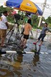 En TVbesättning är i en översvämmad gata av Pathum Thani, Thailand, i Oktober 2011 royaltyfri foto
