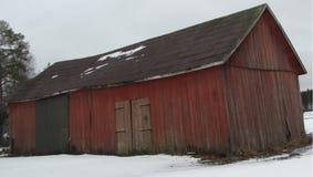 En typisk finlandssvensk byggnad med breda och normala dörrar var korn och jordbruks- maskineri lagras royaltyfri bild