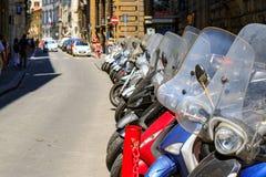 En typisk gata av Florence med motorcykelsparkcyklar som in parkeras Royaltyfri Foto