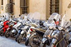 En typisk gata av Florence med motorcykelsparkcyklar som in parkeras Royaltyfria Foton