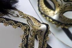 En typisk Venetian karnevalmaskering, guld med svart, reflekteras i spegeln Arkivbild