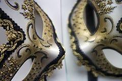 En typisk Venetian karnevalmaskering, guld med svart, reflekteras i spegeln Arkivfoton