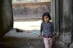 En tystlåten flicka och valp som spelar på templet Arkivfoto