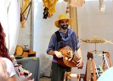 En ullbonde- och musikerman spelar ett kabelinstrument royaltyfria foton