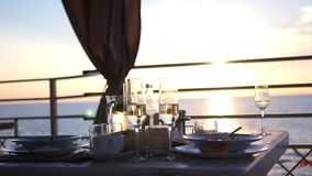 En un café en la puesta del sol por el mar, cubra una tabla con las placas y los vidrios HD, 1920x1080 Cámara lenta almacen de video