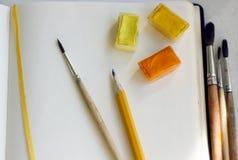 En un cuaderno abierto son las pinturas de la acuarela, los cepillos y un lápiz fotos de archivo