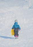 En un día de invierno soleado en la colina de la nieve con el niño del trineo Foto de archivo libre de regalías