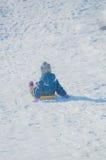 En un día soleado en una colina nevosa un niño con un trineo Fotografía de archivo libre de regalías