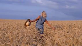 En un día soleado, una mujer está caminando a lo largo de un campo de trigo con un vestido blanco, en un sombrero de paja en un c metrajes