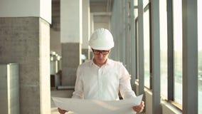 En un emplazamiento de la obra, un trabajador o un ingeniero o un arquitecto controla el diseño y la construcción del edificio co metrajes