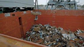 En un envase grande con las piezas del hierro de la caída de la ruina del metal, un imán mecánico del edificio envía la basura en almacen de video