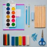 En un fondo azul, accesorios y una pluma, lápices coloreados, un par de compases, un par de compases, un par de tijeras de la esc fotografía de archivo libre de regalías