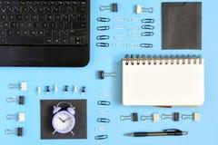 En un fondo azul, los clips de papel y los clips de papel se arreglan cuidadosamente Cuaderno vacío en las primaveras para escrib Fotos de archivo libres de regalías
