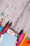 En un fondo de madera con un lugar para escribir es una disposición de lápices, de cuadernos y de papeles coloreados Imagen de archivo libre de regalías