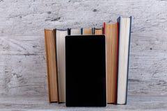 En un fondo de madera es una pila de libros y de una tableta negra El concepto de educación imagen de archivo libre de regalías