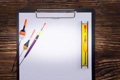 En un fondo de madera oscuro, es una tableta con una hoja de papel blanca y los objetos para pescar, el flotador y los trastos pa fotos de archivo