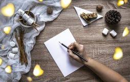 En un fondo de madera una hoja y una pluma escriben, las melcochas y los dulces, una taza con el cacao, mentiras un muñeco de nie fotografía de archivo libre de regalías