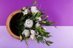 En un fondo púrpura, un ramo de un eustoma japonés blanco en un pote de madera Visión desde arriba imagen de archivo